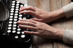 Hands writing on old typewriter over wooden table Royalty Free Stock Images
