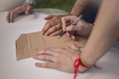 Hands writing in a piece of cardboard. Hands writing with a pen in a piece of cardboard royalty free stock photography