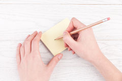 Hands writing on reminder notes with wood pencil Stock Photography