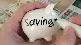Hands writing savings tips on the piggy bank. Hands writing savings tips on a piggy bank stock footage