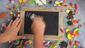 Hands writting trick or treat. Hands writting happy halloween on blackboard, halloween scene stock video footage
