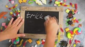 Hands writting trick or treat. On blackboard, halloween scene stock video footage
