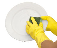 Hands in yellow gloves. Wash white plate Royalty Free Stock Photography