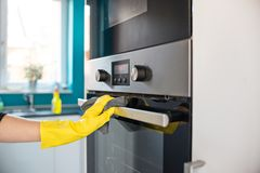 Hands in yellow protective rubber gloves cleaning oven. Closeup on woman's hands in yellow protective rubber gloves cleaning oven with rag Royalty Free Stock Images