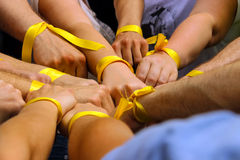 Hands with yellow ribbons together. Royalty Free Stock Image