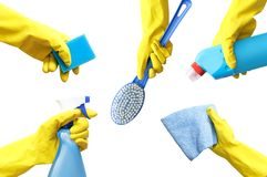Hands in yellow rubber gloves hold a detergent, a rag, a bottle of spray, a brush, a sponge for cleaning the isolate. stock photo