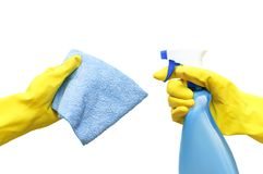 Hands in yellow rubber gloves are holding a detergent and a rag for cleaning the isolate. royalty free stock image