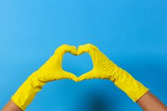 Hands in yellow rubber gloves making heart shape with fingers, on blue background royalty free stock images