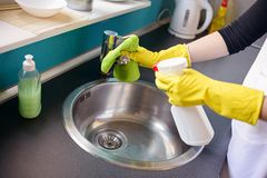 Hands in yellow rubber gloves washing the tap Royalty Free Stock Images