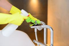 Hands with yellow rubber protective gloves cleaning bath mixer Stock Photo