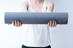 Hands on a yoga mat. Woman holding a yoga mat on white background Royalty Free Stock Image