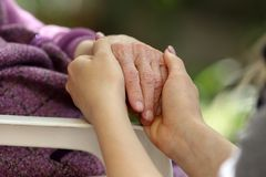 Hands of young adult and senior women. Senior and young holding hands outside. Elderly concept.  royalty free stock image