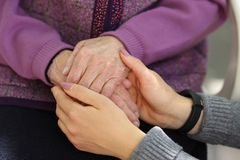 Hands of young adult and senior women. Senior and young holding hands outside. Elderly concept stock photo