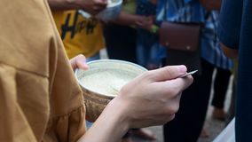 Hands of young Asian people offering food in Monk`s alms bowl.  stock footage