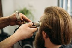 The hands of young barber making haircut to attractive bearded man in barbershop stock image