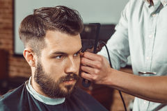 The hands of young barber making haircut to attractive man in barbershop Royalty Free Stock Image