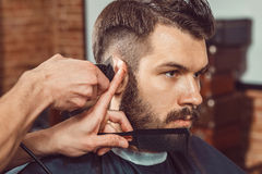 The hands of young barber making haircut to attractive man in barbershop Royalty Free Stock Photo