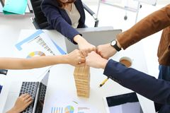 Hands of young business people giving fist bump together to greeting complete dealing in office. Success and teamwork concept. Hands of young business people stock photography