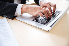 Hands of young businessman using laptop at the table Royalty Free Stock Photos