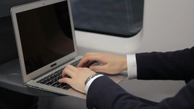 Hands of young businessman who is typing email on his laptop keyboard while traveling in train. The man is wearing black suit and wrist watches and his brand stock video footage