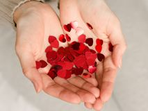 Hands of a young caucasian girl hold small hearts. Close up. Love and happiness are in our own hands Royalty Free Stock Photos