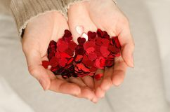 Hands of a young caucasian girl hold small hearts. Close up. Love and happiness are in our own hands Stock Photography