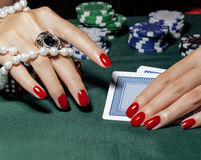 Hands of young caucasian woman with red manicure at casino green table close up Stock Photography