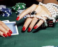 Hands of young caucasian woman with red manicure at casino table Royalty Free Stock Photo