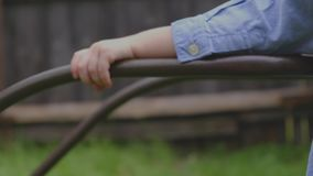 Hands of a young child in a blue shirt holding the handle stock footage