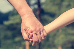 Hands of young child and old senior Royalty Free Stock Photo