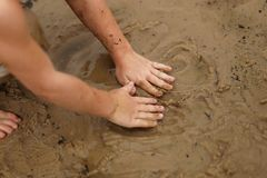 Hands of Young Child Playing in Wet Sand at the Beach Royalty Free Stock Photography