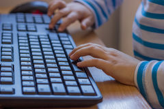 Hands of young child using keyboard to playing 3 Stock Photography