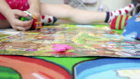 Hands of young children leads fingers on the game board picking up different toys stock video