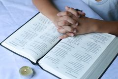 The hands of a young Christian child are folded in prayer over t. He book the Holy Bible Stock Images