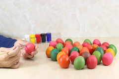 Hands of young christian coloring eggs on marble top background preparing for easter day. Stock Photo