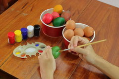 Hands of young christian man is coloring eggs with paintbrush on wooden table. Easter day concept. Royalty Free Stock Images