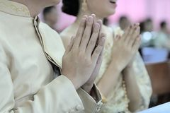 Hands of young couple praying in Thai wedding ceremony. Selective focus and shallow depth of field. Hands of young couple praying in Thai wedding ceremony Royalty Free Stock Photography