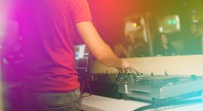 The hands of a young DJ operate a remote in a nightclub creating contemporary music.  Royalty Free Stock Image