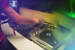 The hands of a young DJ operate a remote in a nightclub creating contemporary music.  Royalty Free Stock Photography