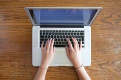 Hands of young female person typing on laptop. On empty wooden table stock photography
