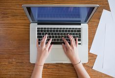 Hands of young female person typing on laptop. Blank paper sheets located nearby royalty free stock images