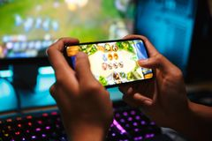 Hands of young gamer boy playing video games on smartphone and c. Omputer in dark room wearing headphones and using backlit colorful keyboard royalty free stock photos