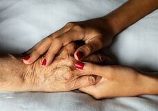 The hands of a young girl caress the wrinkled hand of her grandmother