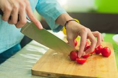 Hands of a young girl chop the cherry tomatoes on a wooden cutting board on a green table in a home setting Stock Photography