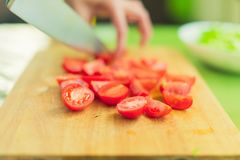 Hands of a young girl chop the cherry tomatoes on a wooden cutting board on a green table in a home setting Stock Image
