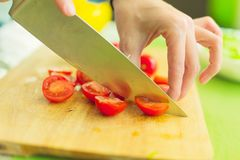 Hands of a young girl chop the cherry tomatoes on a wooden cutting board on a green table in a home setting Stock Photos