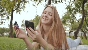 The hands of a young girl close-up, lying on nature, makes purchases via the Internet with a credit card using a laptop. And a smartphone stock video footage