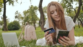 The hands of a young girl close-up, lying on nature, makes purchases via the Internet with a credit card using a laptop. And a smartphone stock video