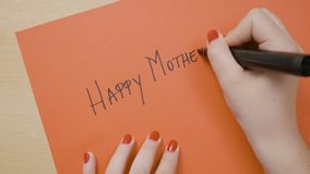 Hands of a young girl daughter writing happy mother s day on a red paper with black marker - stock video