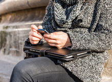 Hands of a young girl holding a smartphone and a tablet and typing Royalty Free Stock Images